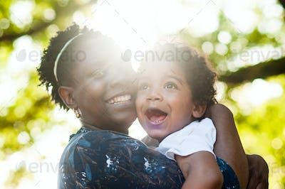 African mom smiling to the camera  holding her toddler boy in her arms
