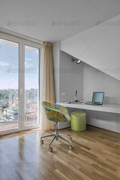 Desk and Armchair Near to French Window in the Children's Bedroom in the  Attic with Wooden Floor