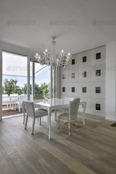 Modern Dining Table in a Living Room with Old Chandelier overlooking on the Terrace