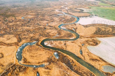 Aerial View Of Dry Grass And Partly Frozen River Landscape In Late Autumn Day. High Attitude View