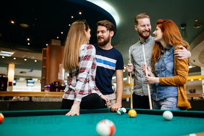 Happy young friends playing snooker and billiards