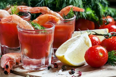 Shrimp cocktail in small glasses, cherry tomatoes, dill, parsley and lemon with salt