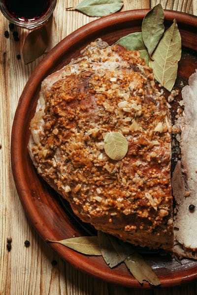 Baked ham with spices on a clay plate on a wooden table, top view