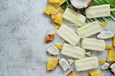 Homemade pineapple coconut popsicles on stone background. Summer food concept with copy space