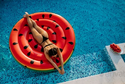 Pool Float woman relax in swimming pool on summer vacations