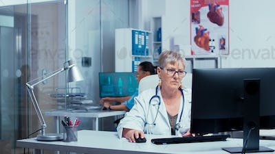 Experienced senior woman doctor working on PC