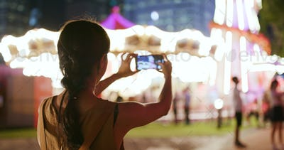 Woman taking photo and video in amusement park at night
