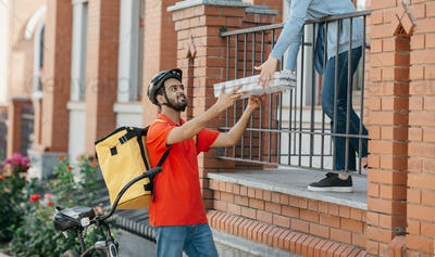Meeting courier and client. Smiling deliveryman in helmet with big yellow backpack on bicycle