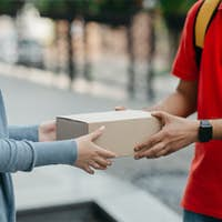 Online shopping and home delivery. Woman takes a box from courier with backpack