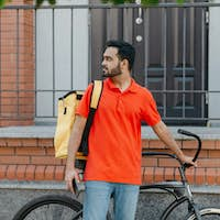 Work in city. Serious deliveryman with beard with backpack and bicycle, holding smartphone and