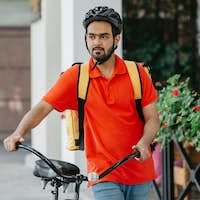 Business, work and delivery. Guy with beard in helmet with backpack and bicycle walks down the