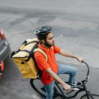 Online delivery service. Courier in helmet with big yellow backpack on bicycle