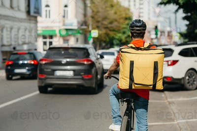 Male courier with helmet and big yellow backpack ride on bicycle along road on street