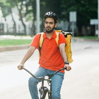 Portrait of male courier on bicycle with backpack. Young guy in helmet on road