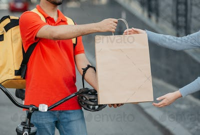 Goods delivery at city. Girl takes a paper bag from courier with big yellow backpack and bicycle