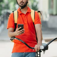 Online map application for courier for work. Serious guy with beard with backpack, looks at