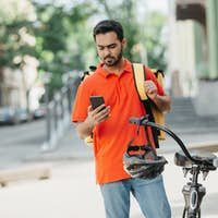 Order received. Guy in uniform with yellow backpack looks at smartphone, standing near a bicycle