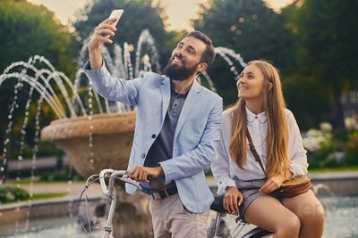 A couple on a date make selfie over fountain background.