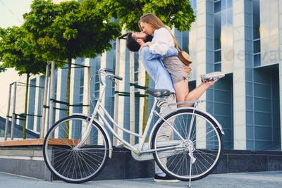 A man hugs a woman over modern building background.