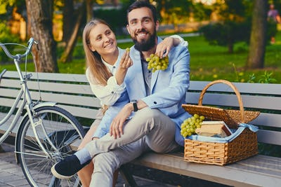 Couple eats grape on a bench in a park.