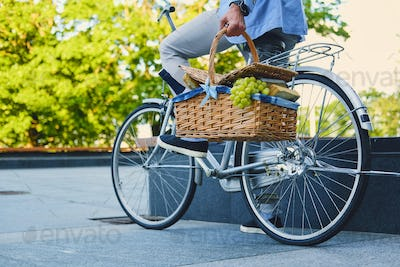 A man on a city bicycle holds picnic basket.