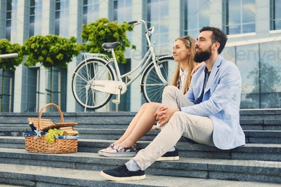 A couple sits on a step with picnic basket.