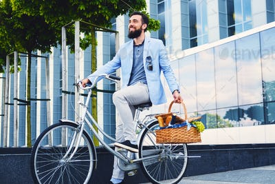 Man on a city bicycle holds picnic basket.