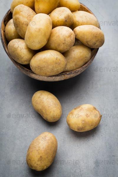 New potato on the bowl, gray background.