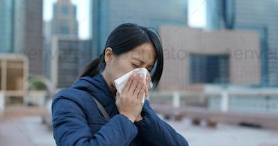 Sick woman sneezing at outdoor