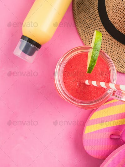 Straw hat, fli flops and red smoothie on pink