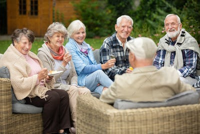 Group of senior friends sitting together in the garden during spring party