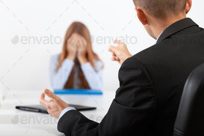 Depressed young woman during a conversation with the boss who points out her mistakes