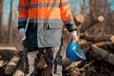 Forestry technician holding protective helmet and clipboard notepad