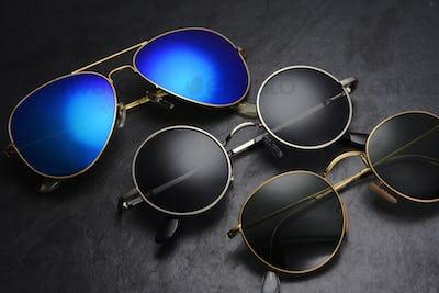 Different sunglasses on black slate background