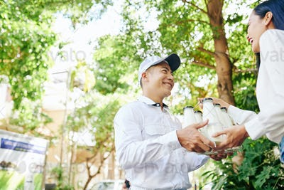 Delivery man giving milk bottles to woman