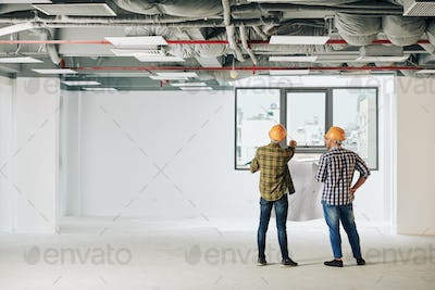 Construction engineers with blueprint