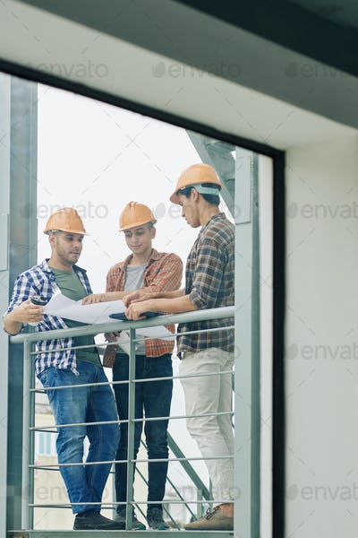 Builders checking building blueprint