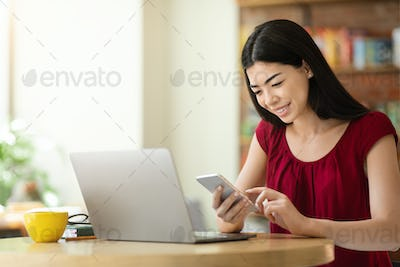 Useful App. Asian Girl Using Smartphone And Laptop While Sitting In Cafe