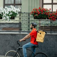 Courier carry out orders for delivery of goods. Man in helmet and big yellow backpack rides bicycle