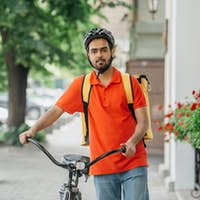 Bike, city and food delivery concept. Courier with beard, in helmet and bag, walks with bicycle down