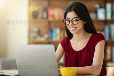 Online education concept. Beautiful asian girl studying remotely on laptop at cafe