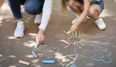 Unrecognizable Mother And Daughter Drawing Using Chalks Having Fun Outside