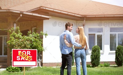 Newlywed couple standing in front yard of their new residential property, blank space