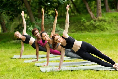 Morning yoga class. Diverse girls in sportswear performing side plank exercise outside