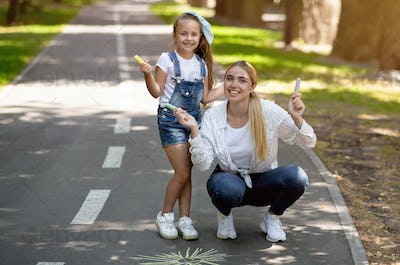 Mother And Daughter Posing Holding Chalks Drawing In City Park