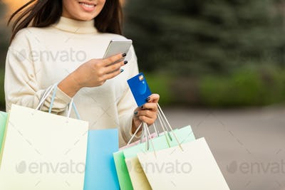 Asian girl with credit card and phone in the city center