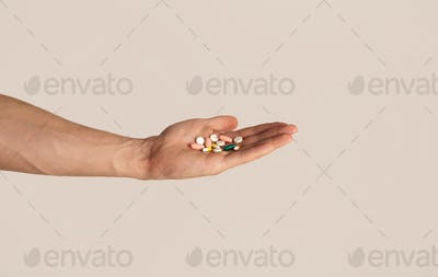 Unrecognizable young guy holding heap of pills in his hand over light background, closeup