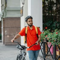 Courier with beard, protective helmet and yellow bag, walking the street with bicycle and looking