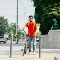 Courier and city traffic. Guy with beard in protective helmet with yellow backpack and bicycle