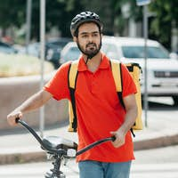 Delivery to home or office. Young man in protective helmet with backpack with bicycle looking for